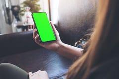 Vrouwen` s handen die zwarte mobiele telefoon met het lege groene Desktopscherm houden in koffie royalty-vrije stock fotografie