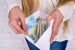 Vrouwen` s handen met envelophoogtepunt van dollar Stock Foto's