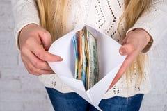 Vrouwen` s handen met envelophoogtepunt van dollar en euro Stock Fotografie