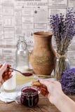 Vrouwen` s handen met lepel en het eigengemaakte koekje van de suikerhoning Frambozenjam in kruik, unch lavendel op een houten ac Royalty-vrije Stock Fotografie
