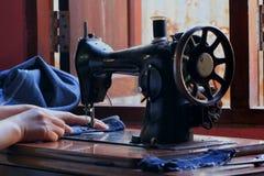 Vrouwen` s handen van naaister die naaimachine met behulp van stock foto