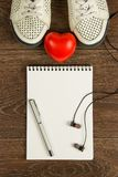 Vrouwen` s schoenen, hart, pen, zwarte hoofdtelefoons en wit notitieboekje F Stock Foto