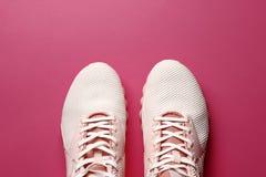 Vrouwen` s tennisschoenen op een gekleurde achtergrond stock foto