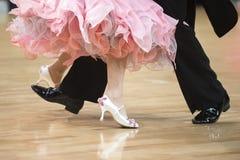 Vrouwen` s voeten tussen man ` s voeten die op parketvloer dansen stock afbeelding