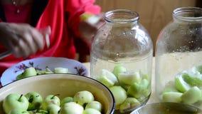 Vrouwen scherpe appelen voor het koken van ingeblikte compote stock videobeelden