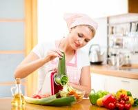 Vrouwen scherpe groenten met apparaat bij de keukenlijst stock afbeelding
