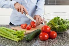 Vrouwen scherpe tomaat stock afbeelding