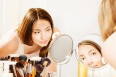 Vrouwen schoonmakend gezicht met katoenen die stootkussen in spiegel wordt gezien stock foto's