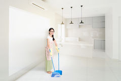 Vrouwen Schoonmakend huis met bezem stock afbeeldingen