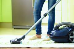Vrouwen schoonmakend huis met stofzuiger Stock Foto's