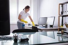 Vrouwen Schoonmakende Computer in Bureau royalty-vrije stock foto