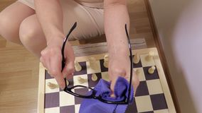 Vrouwen schoonmakende glazen dichtbij schaakbord stock video