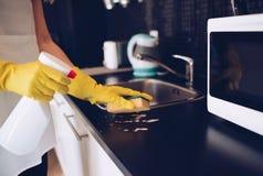 Vrouwen schoonmakende keukenkasten met spons stock afbeelding