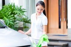 Vrouwen schoonmakende koplamp bij autowasserette Royalty-vrije Stock Afbeelding
