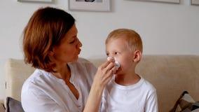 Vrouwen schoonmakende neus aan haar zoon stock footage
