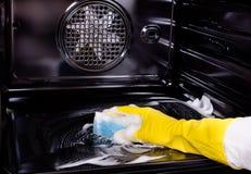 Vrouwen schoonmakende oven stock foto