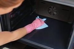 Vrouwen schoonmakende oven met vod in keuken stock afbeelding