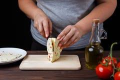 Vrouwen snijdende kaas op hakbord Eigengemaakte keuken, gezondheid royalty-vrije stock fotografie