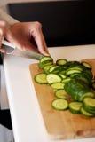 Vrouwen snijdende komkommer Stock Foto