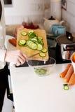 Vrouwen snijdende komkommer Stock Afbeeldingen