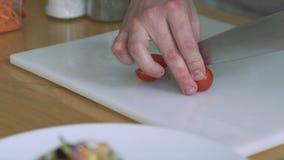 Vrouwen snijdende tomaat-kers die op een restaurantkeuken voorbereidingen treffen langzaam stock video