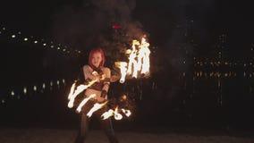 Vrouwen spinnende brandende ventilators tijdens fireshow bij schemer stock footage
