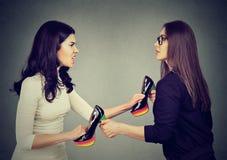 Vrouwen tearing vechten apart trekkend schoenen Stock Afbeeldingen
