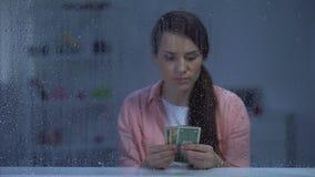 Vrouwen tellend geld op middelbare leeftijd achter regenachtig venster, slechte begroting, armoede stock videobeelden