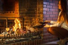 Vrouwen thuis open haard die brand met blaasbalgen maken Royalty-vrije Stock Afbeeldingen