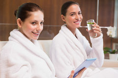 Vrouwen in van de badjassen drinkwater en tekst overseinen Stock Foto