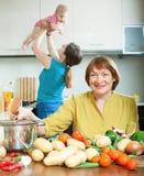 Vrouwen van drie generaties in binnenlandse keuken Stock Foto's