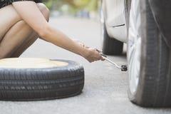 Vrouwen veranderend wiel op een kant van de weg Royalty-vrije Stock Foto's