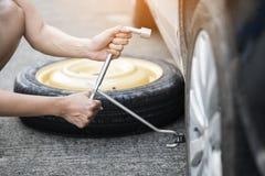 Vrouwen veranderend wiel op een kant van de weg Royalty-vrije Stock Foto