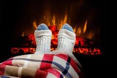 Vrouwen verwarmende voeten in wollen sokken dichtbij open haard stock fotografie