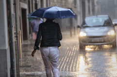 Vrouwen walkng onder de regen die paraplu dragen Royalty-vrije Stock Afbeelding