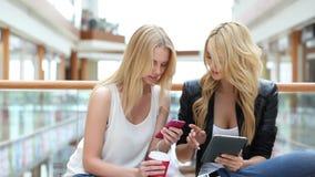 Vrouwen in wandelgalerij die smartphone gebruiken stock videobeelden