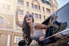 Vrouwen wawing hand aan somebody die uit autoraam kijken royalty-vrije stock foto's