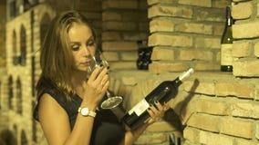 Vrouwen winemaker ruikend glas van rode wijn en het houden van fles in kelder in hand Jonge vrouw die en het drinken rood proeven stock video
