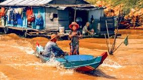 Vrouwenaandrijving een boot met kind op Tonle-Sapmeer Stock Fotografie