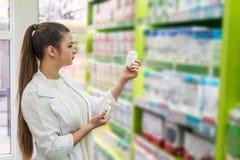 Vrouwenapotheker die container met tabletten bekijken royalty-vrije stock foto
