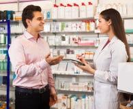 Vrouwenapotheker en bezoeker bij de apotheek stock fotografie
