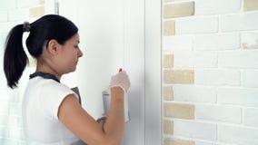 Vrouwenarbeider die borstel het schilderen muren in de flat of het huis gebruiken Bouw, reparatie en vernieuwing stock videobeelden