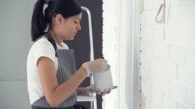 Vrouwenarbeider die borstel het schilderen muren in de flat of het huis gebruiken Bouw, reparatie en vernieuwing stock footage