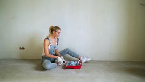 Vrouwenarbeider die rol in een emmer met behulp van om de muren in de flat of het huis te schilderen Bouw, reparatie en vernieuwi stock video