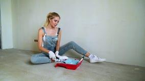 Vrouwenarbeider die rol in een emmer met behulp van om de muren in de flat of het huis te schilderen Bouw, reparatie en vernieuwi stock footage