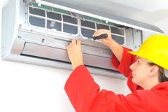 Vrouwenarbeider het aanpassen airconditionersysteem Stock Afbeelding