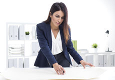 Vrouwenarchitect die met blauwdrukken werken terwijl status dichtbij haar Stock Foto