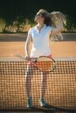 Vrouwenatleet in de sexy eenvormige racket van het greeptennis bij netto royalty-vrije stock foto