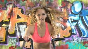 Vrouwenatleet die intense training op gymnastiekfiets doen stock videobeelden
