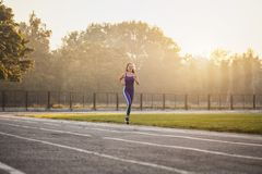 Vrouwenatleet op een ochtend in het stadion in werking dat wordt gesteld dat stock foto